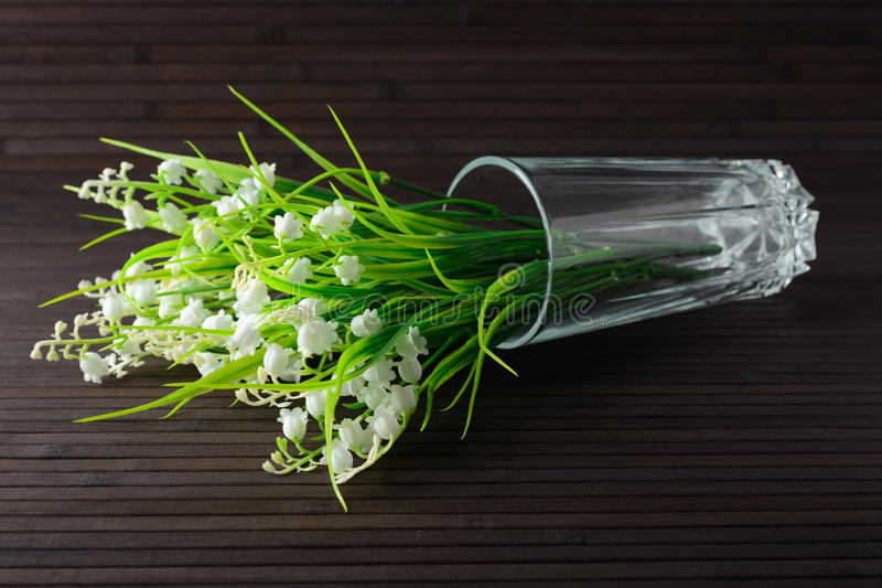 Bouquet artificial lily of the valley in a glass. Bouquet of artificial lily in a glass on a bamboo background royalty free stock photo