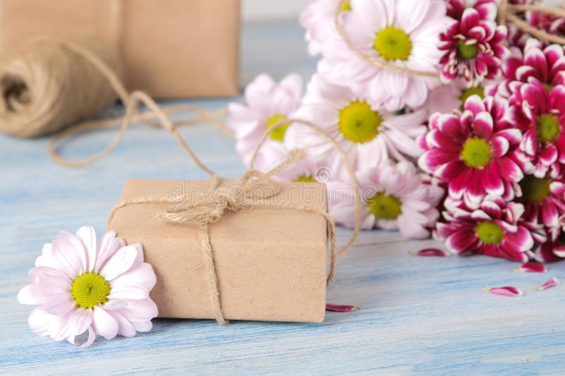 Bouquet of autumn flowers of pink chrysanthemums and gift boxes on a blue wooden table royalty free stock photos