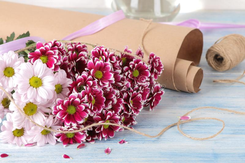 Bouquet of autumn flowers of pink chrysanthemums and gift boxes on a blue wooden table stock images