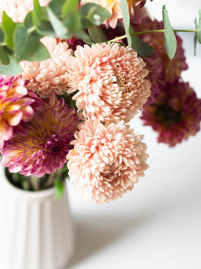 Bouquet of autumn flowers in a vase on the table. Peach asters and burgundy with yellow dahlias with eucalyptus branches in a vase stock images