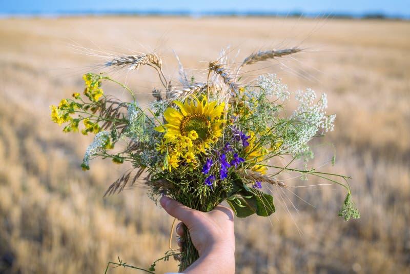 Bouquet av vilda blommor i flickans hand fotografering för bildbyråer