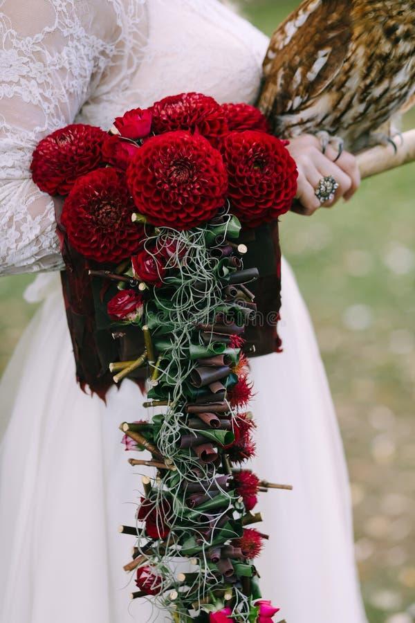 Bouquet avec des dahlias de Bordeaux sur la main de jeune mariée Décoration de mariage fleurit des dahlias photographie stock libre de droits