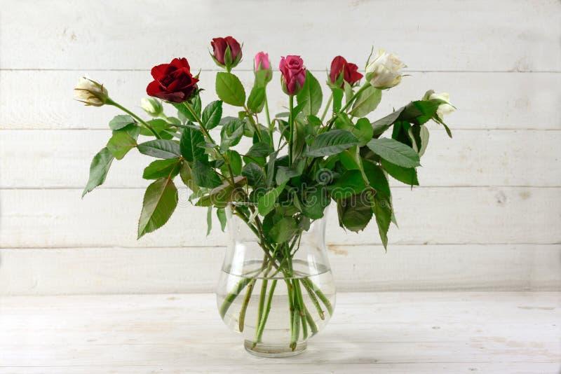Bouquet avec des roses en rouge, rose et blanc dans un vase en verre sur le bois rustique peint gris-clair, l'espace de copie photos stock