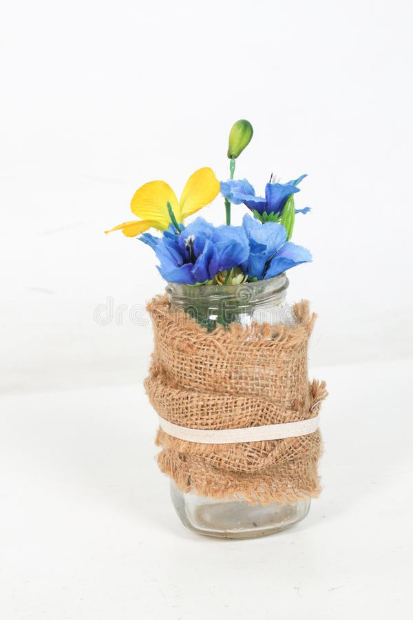 Bouquet avec les roses, les feuilles et l'ornement colorés de paille dans le vase en verre sur le fond blanc vase ornemental avec photographie stock