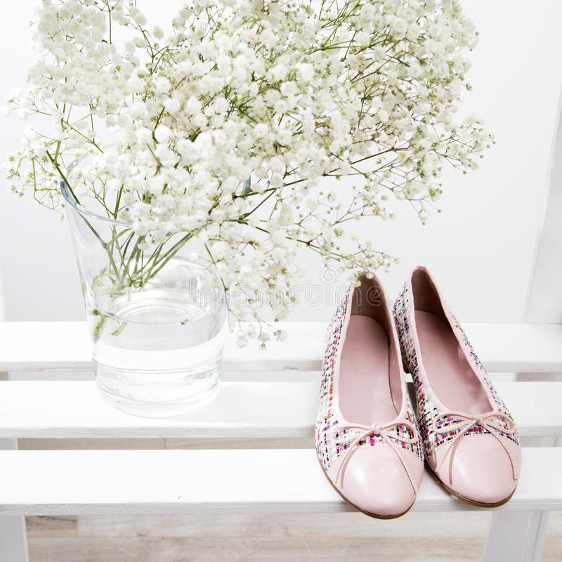 Bouquet of baby`s breath in a transparent glass vase and pink shoes of the bride on a shelf stock photo