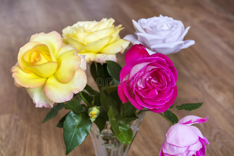 Bouquet of beautiful blooming roses in a glass vase royalty free stock photography