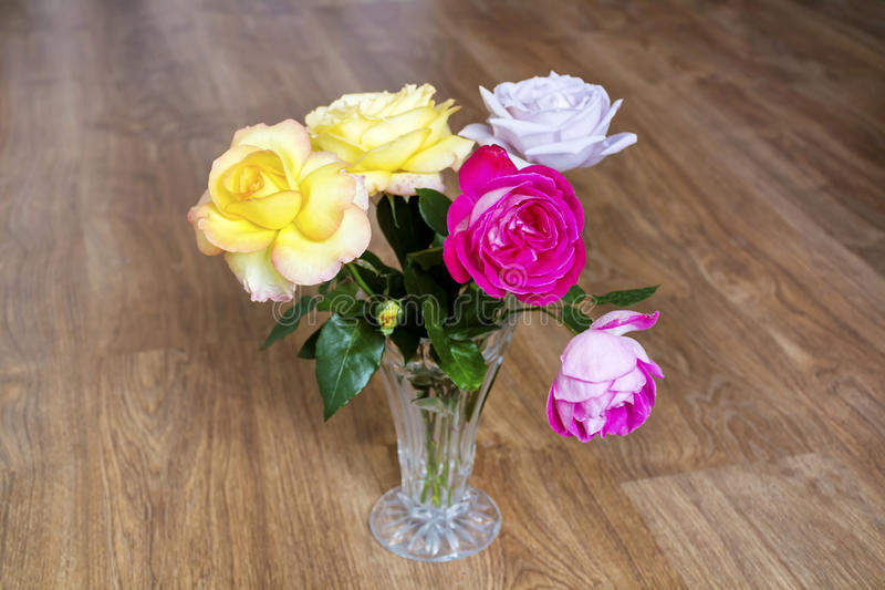 Bouquet of beautiful blooming roses in a glass vase stock photography