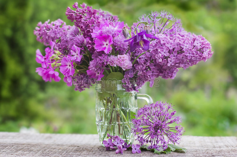 A bouquet of beautiful flowers of lilac on a background of green royalty free stock photos