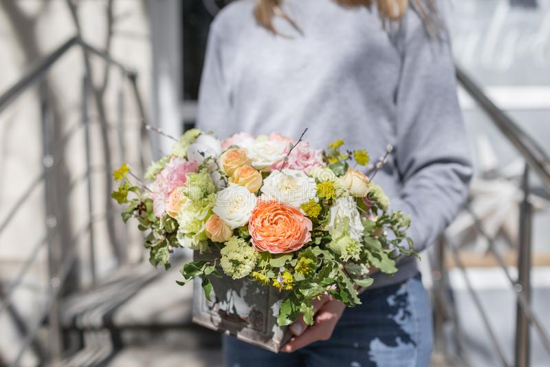 Bouquet of beautiful flowers in women`s hands. Floristry concept. Spring colors. the work of the florist at a flower. Shop stock photography