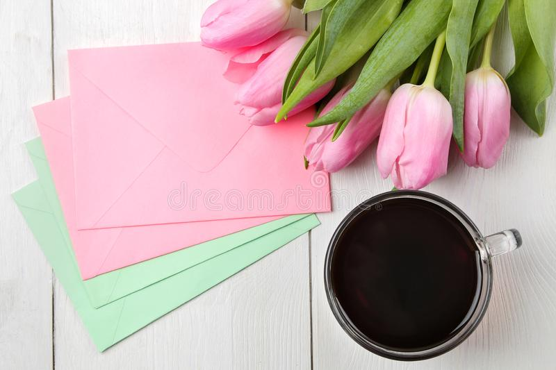 A bouquet of beautiful pink tulips flowers and color envelopes and a cup of coffee on a white wooden table. Spring. holidays. top royalty free stock photos