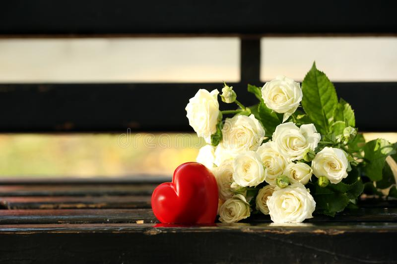 Bouquet of beautiful roses with red heart on wooden bench outdoors stock images