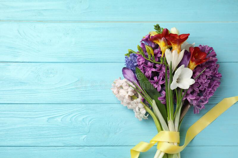 Bouquet of beautiful spring flowers on blue table, top view. Space for text. Bouquet of beautiful spring flowers on blue wooden table, top view. Space for text stock photography