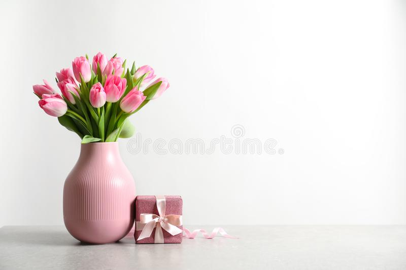 Bouquet of beautiful spring tulips in vase and gift box on table against white background. stock photo