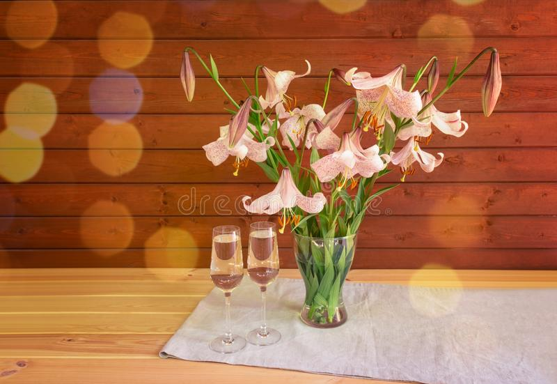Bouquet of beige colored lilies with pink spots in glass  vase and two glasses of champagne. stock photos