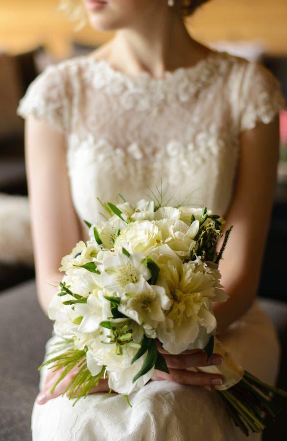 Bouquet blanc dans des mains de la jeune mariée photographie stock