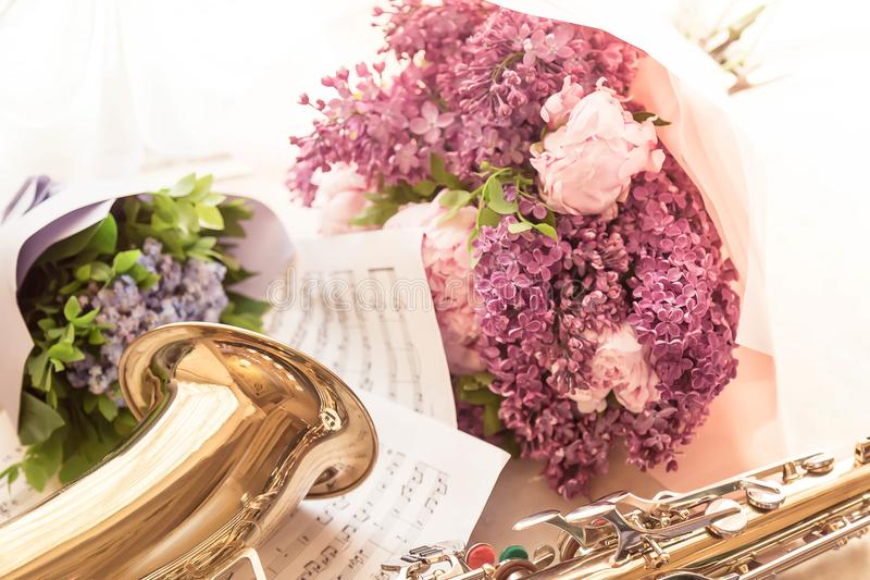 Bouquet of the blossoming lilac for the musician playing a saxophone. Sheets with notes. White background royalty free stock photos