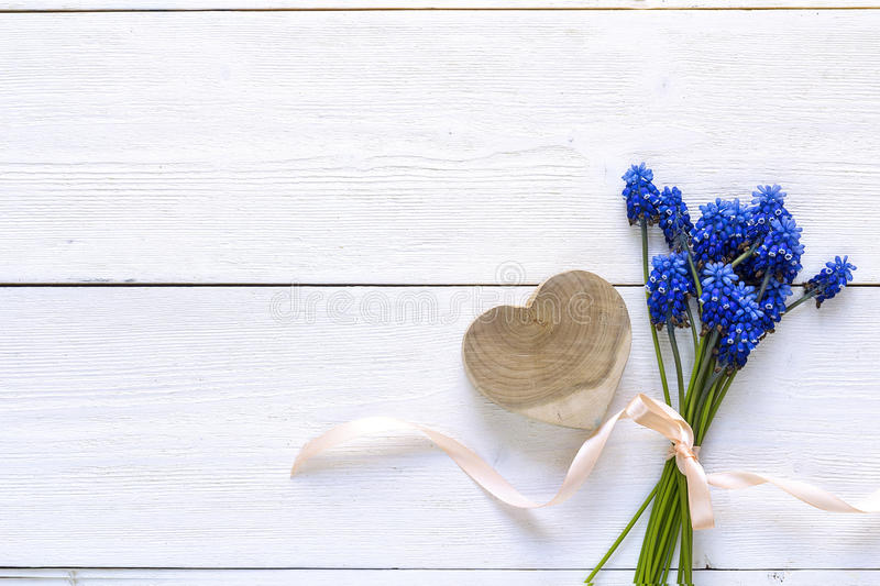 Bouquet of blue muscari flowers with wooden heart on white background. Place for text. Top view. stock photography
