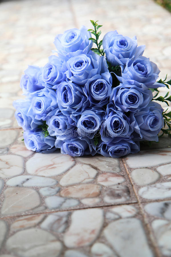 Bouquet of blue rose lying on grey road royalty free stock image