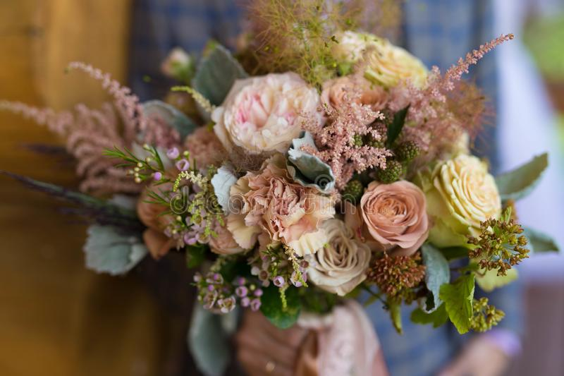 Bouquet for the bride from different flowers. Newlyweds hold a bouquet for the bride from different flowers stock photo