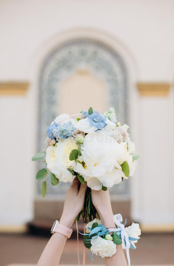 Bouquet bride flowers hands outside architecture arch. Bouquet of bride flowers in hands outside on a background of architecture arch in blur royalty free stock image