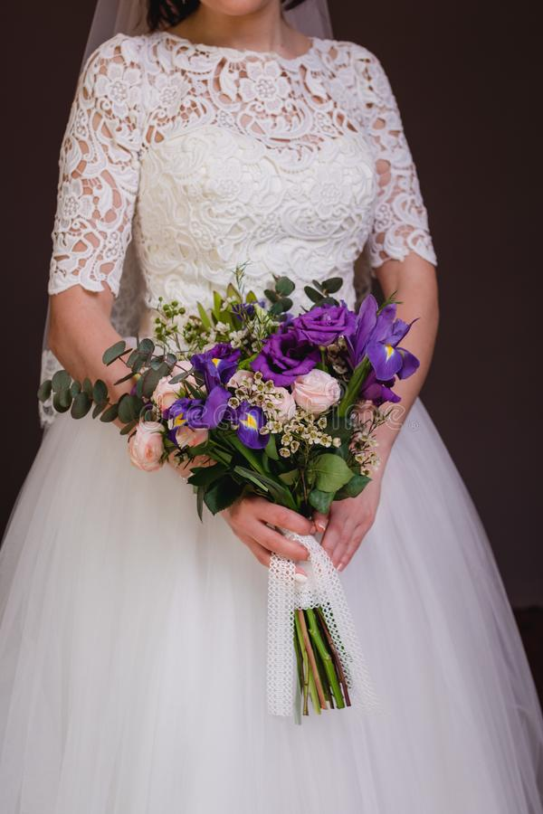 Bouquet of the bride in the hands of wedding rings. the bride is holding a bouquet. stock photography