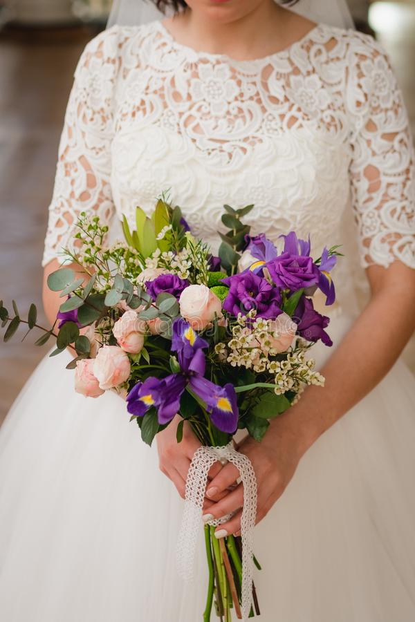 Bouquet of the bride in the hands of wedding rings. the bride is holding a bouquet. stock images