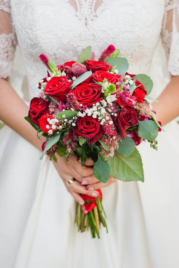 Bouquet of the bride in the hands of wedding rings royalty free stock photo