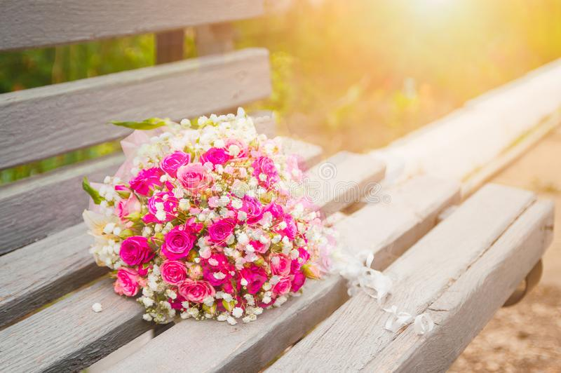 A bouquet of a bride from pink roses lies on a wooden bench in the light of the setting sun royalty free stock photo