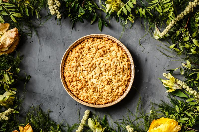Bouquet of bright flowers and apple pie lying on gray background. Flat lay. Top view royalty free stock photos