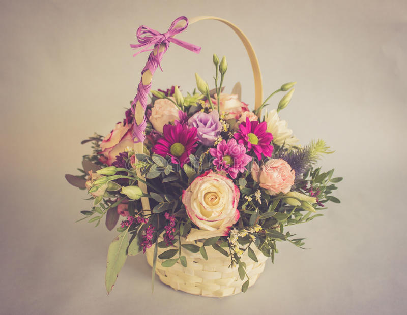 Bouquet of bright flowers in basket in vintage colors stock images