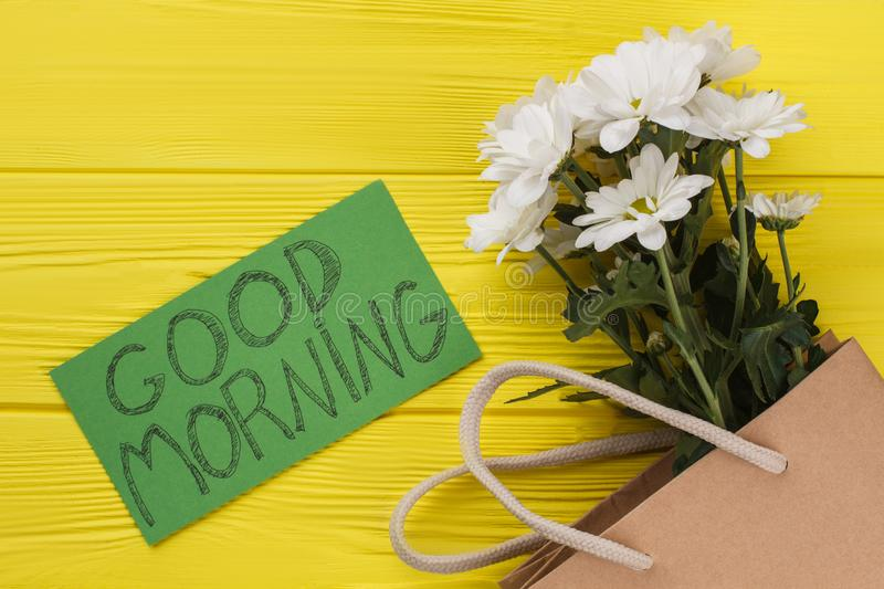 Bouquet of chamomile flowers and good morning wish. Yellow wooden background stock images