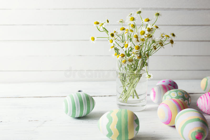 Bouquet of chamomiles in a glass vase and easter eggs in pastel color on white wooden table stock image