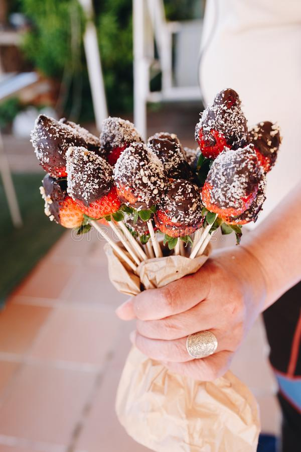 A bouquet of chocolate covered strawberries with different toppings, chocolate coconut cocoa almonds nuts royalty free stock photo