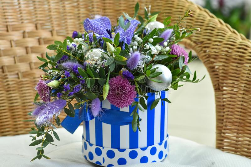 Bouquet of Christmas tree with Christmas decorations and live lilac flowers in a striped basket royalty free stock photo