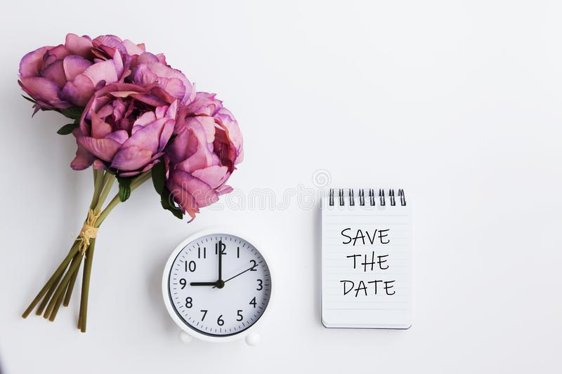 Bouquet, Clock and Note pad with text written - Save the Date stock photos
