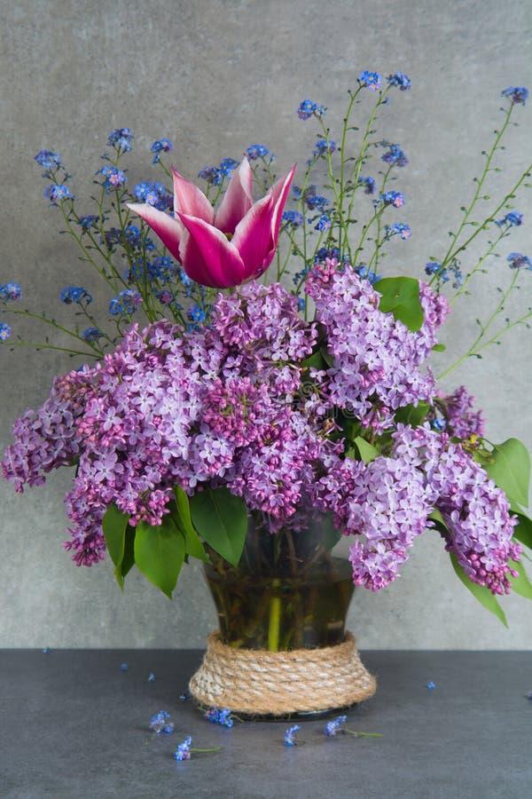 Bouquet coloré dans le vase en verre avec le lilas pourpre, la tulipe rose et photo stock