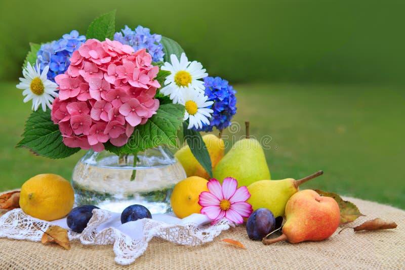 Bouquet coloré de fleurs en vase en verre et fruits mélangés frais image libre de droits