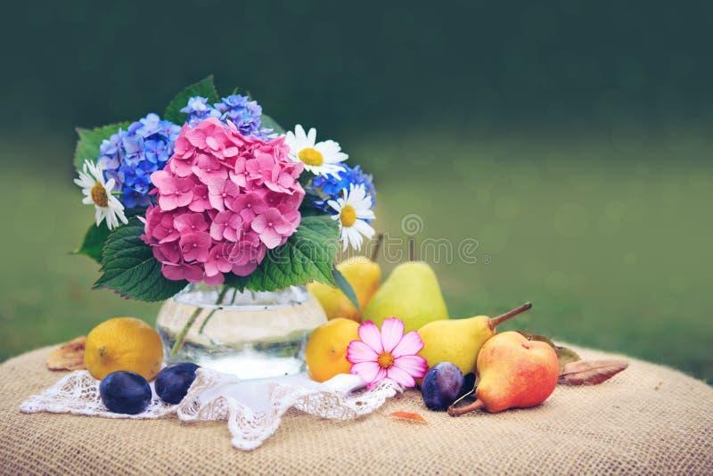 Bouquet coloré de fleurs en vase en verre et fruits mélangés frais images libres de droits