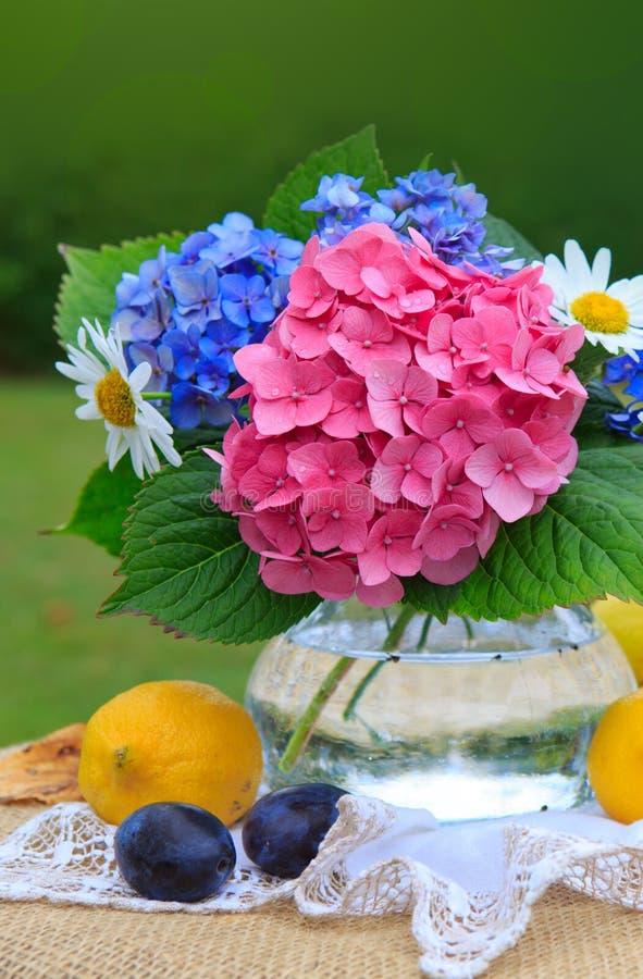 Bouquet coloré de fleurs en vase en verre et fruits mélangés frais images stock