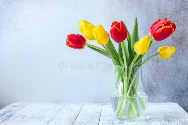Bouquet coloré frais de fleurs de tulipes dans le vase en verre sur la table en bois devant le mur en pierre photo libre de droits