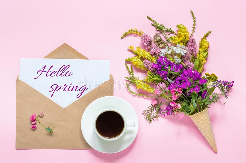 Bouquet of colored flowers in waffle cone, cup of coffee and envelope with card text Hello spring on pink background Greeting card stock photo