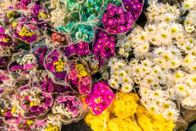 Bouquet of colorful chrysanthemum and other winter flowers put for sale in the bucket in the flower market. stock photography