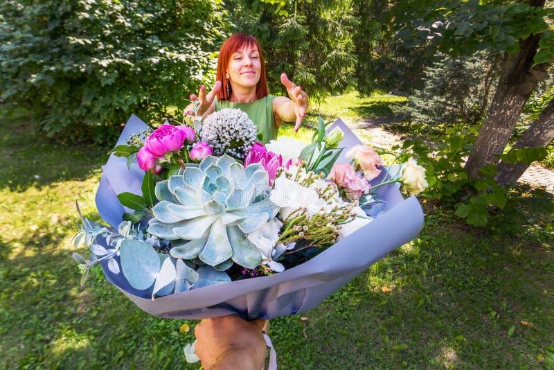 Bouquet comme cadeau La fille rousse reçoit des fleurs comme cadeau a photos libres de droits