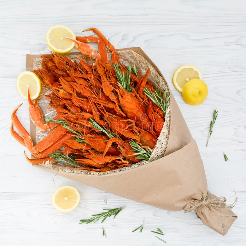 Bouquet consisting of boiled crawfish and crabs with rosemary sprigs and lemon slices on a white wooden table. View from above.  stock photos