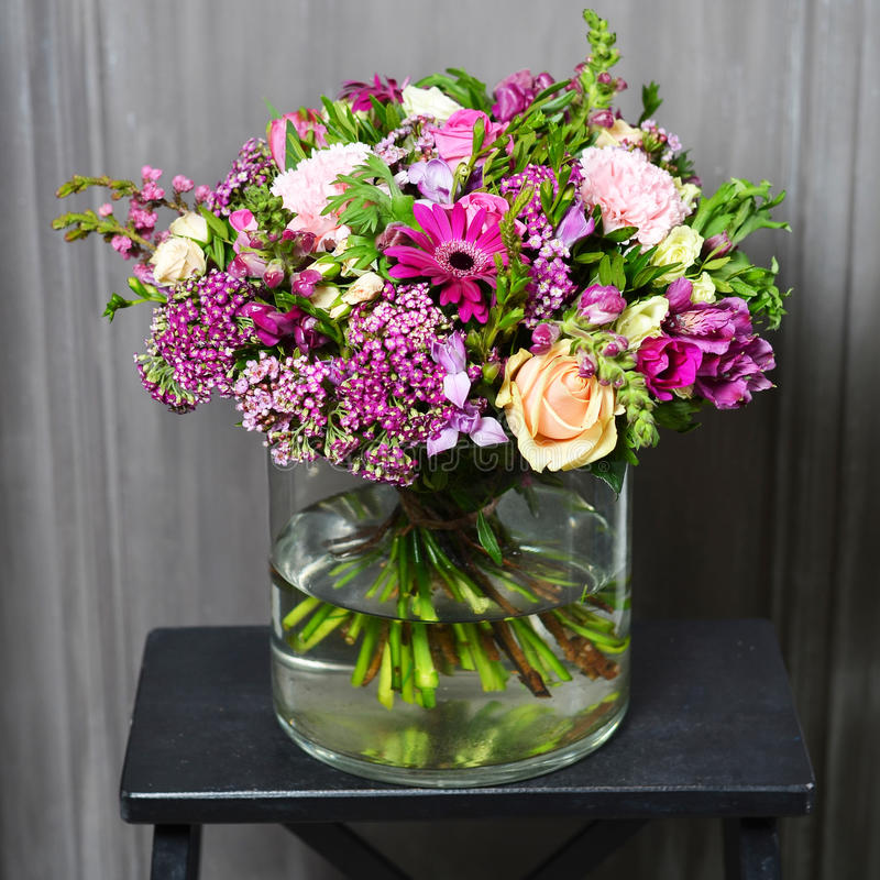 Bouquet with cream roses and purple flowers in a glass vase stock photo
