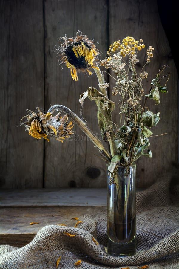 Bouquet défraîchi avec le tournesol et le tansy d'or dans le feu de position dessus image libre de droits