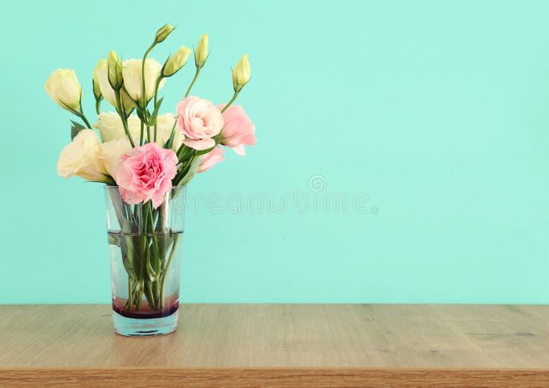 bouquet d'été des fleurs blanches et roses dans le vase au-dessus de la table en bois et du fond en bon état en pastel photo libre de droits