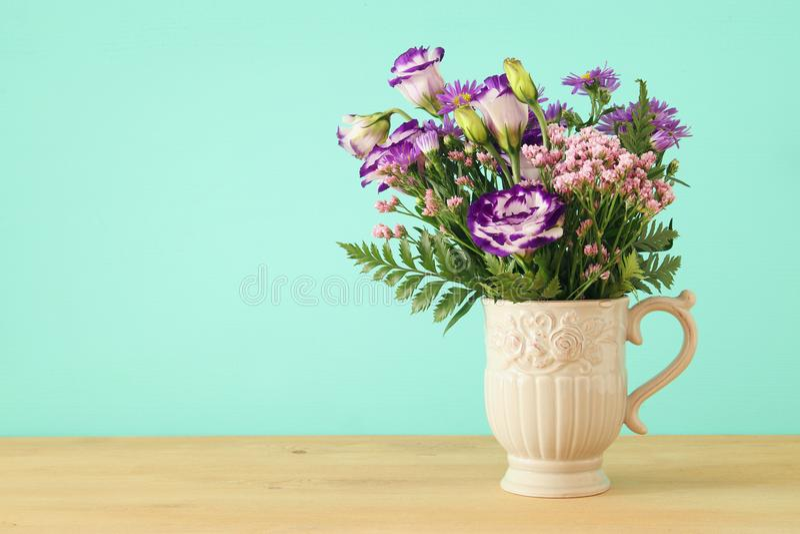 bouquet d'été des fleurs pourpres dans le vase au-dessus du fond en bois de table et de menthe image libre de droits