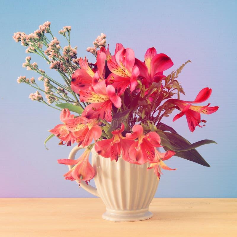 bouquet d'été des fleurs rouges dans le vase au-dessus de la table en bois et du fond bleu images libres de droits