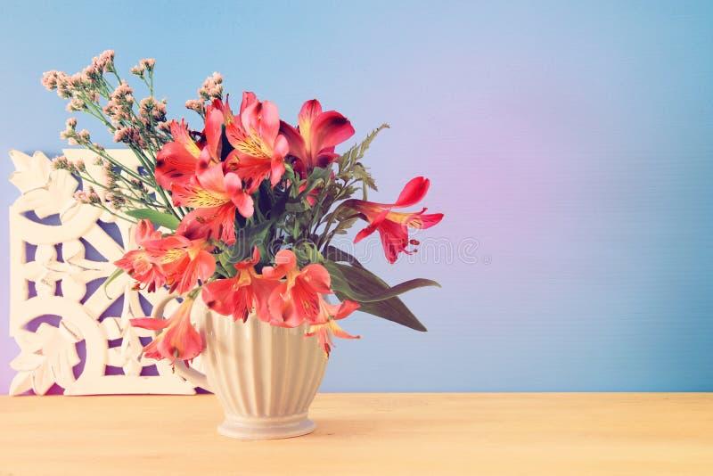 bouquet d'été des fleurs rouges dans le vase au-dessus de la table en bois et du fond bleu photo libre de droits